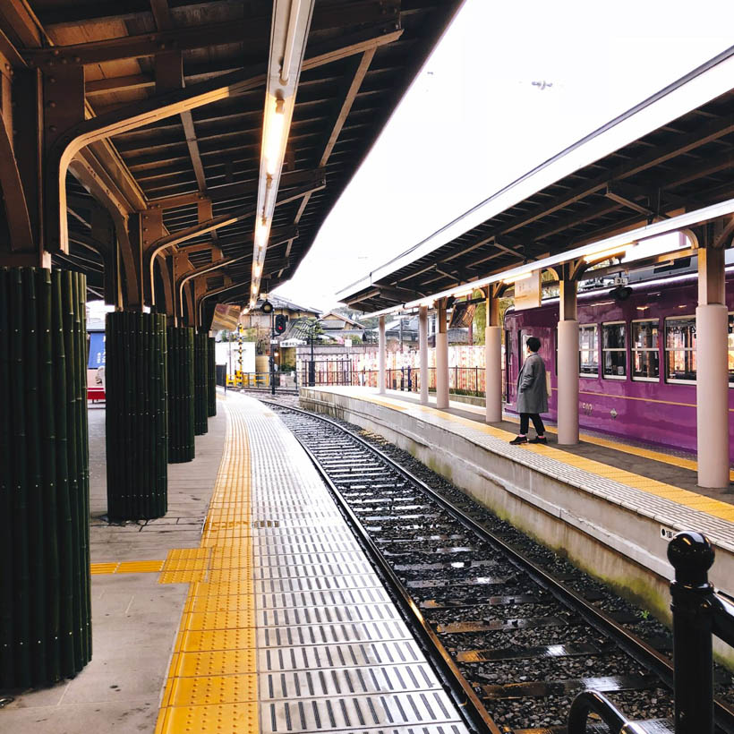 A man waiting on a train in the Arashiyama Train Station in Kyoto, Japan.