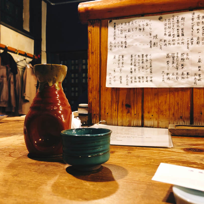 A cup and a small bottle of sake in a small izakaya in the center of Kyoto, Japan.