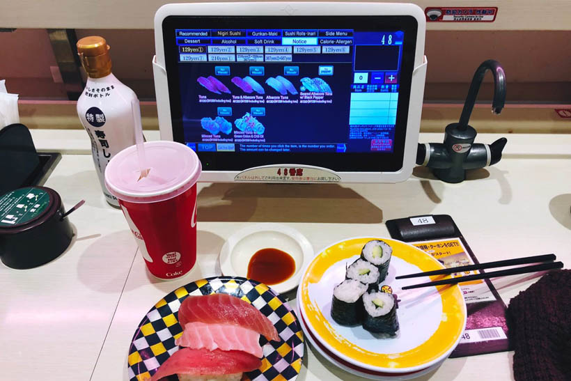 A plate of conveyor belt sushi at a Genki chain restaurant in Shibuya, Japan, with a touch screen that is used to order food, drinks and snacks.