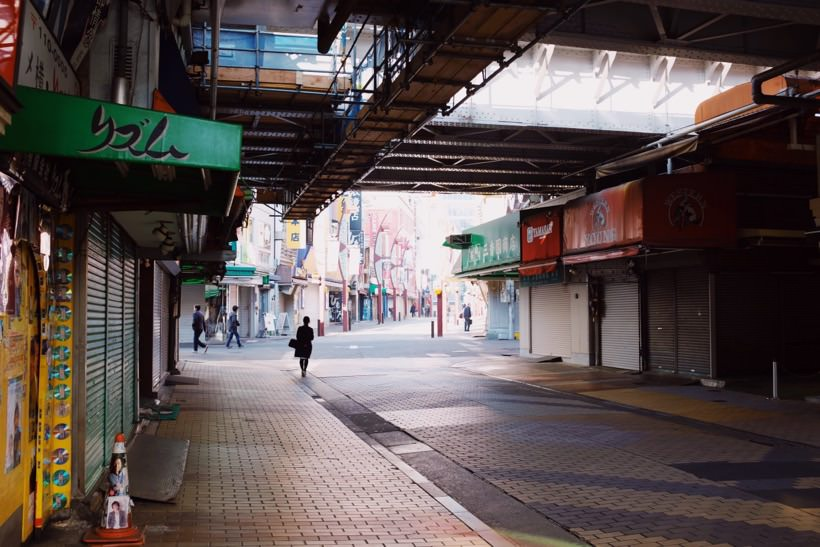 A clean, near empty street underneath a metro line with closed shops in Ueno, Japan.
