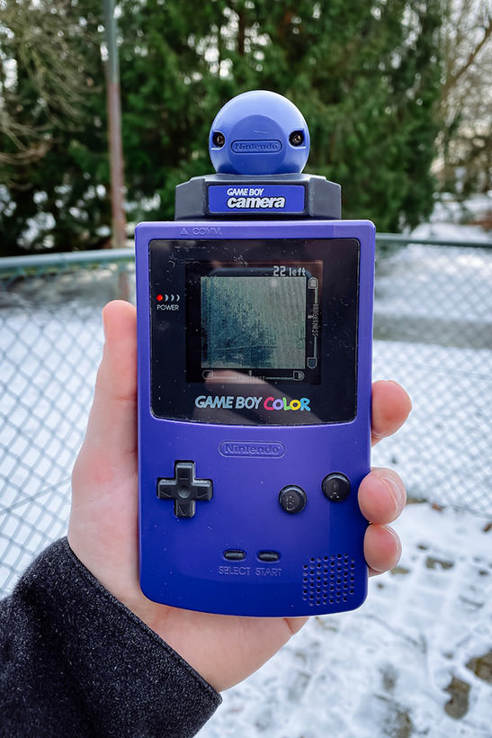 A Game Boy Color with a Game Boy Camera inserted, with the lens pointing at trees in a park in Leuven, Belgium.